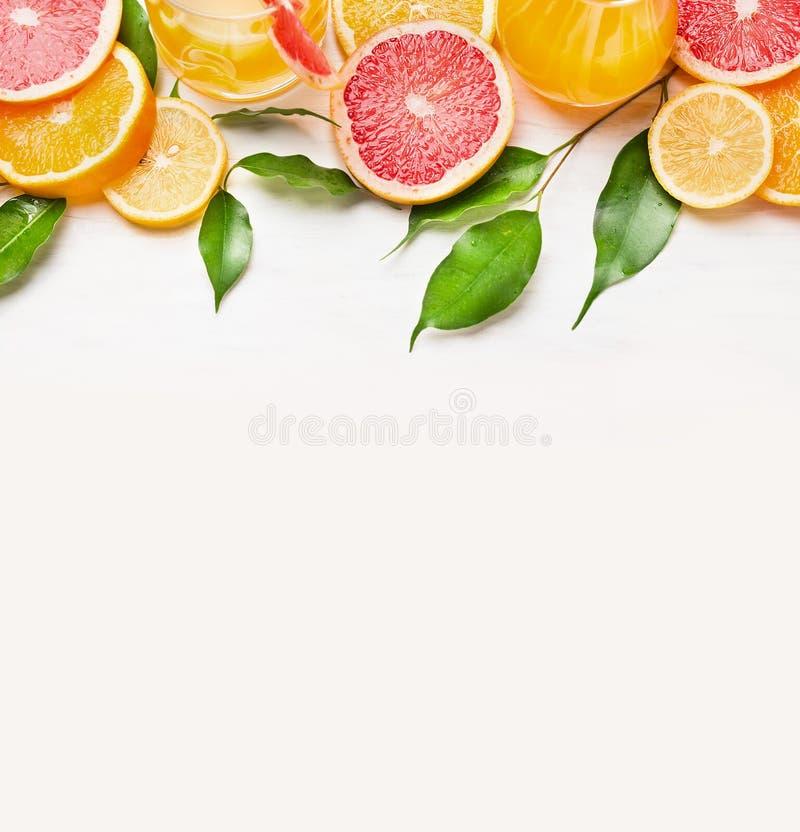 Citrus fruits slices frame on white wooden background stock photo