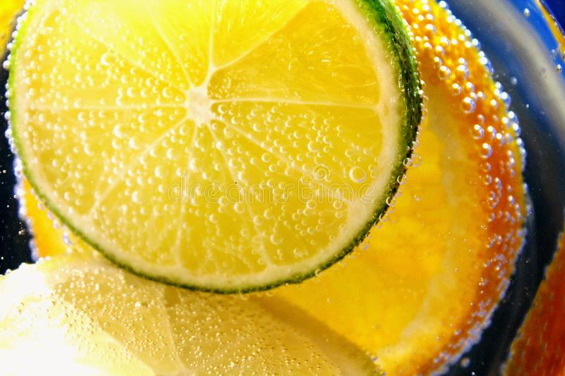 Citrus fruits of - slices orange, lemon, lyme in water with bubles-a refreshing summer vitamin drink. royalty free stock images