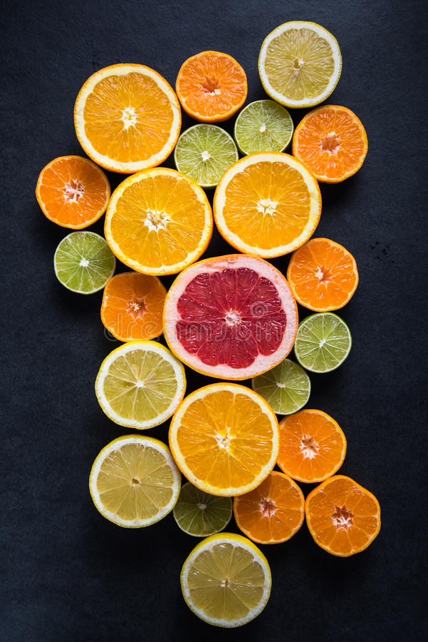 Citrus half cut fruits on dark background royalty free stock images