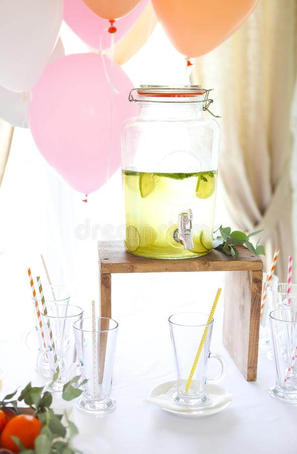 Citrus homemade lemonade in a beverage dispencer. Lemonade on the balloons background. Birthday party royalty free stock photos