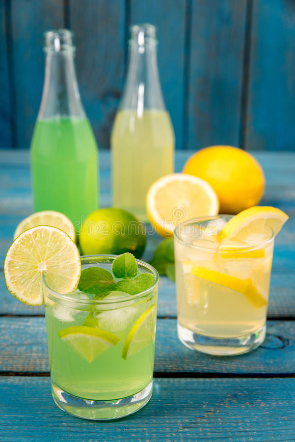 Citrus homemade lemonade. Homemade lemonade with lime, mint in a mason jar on a wooden rustic table stock photos
