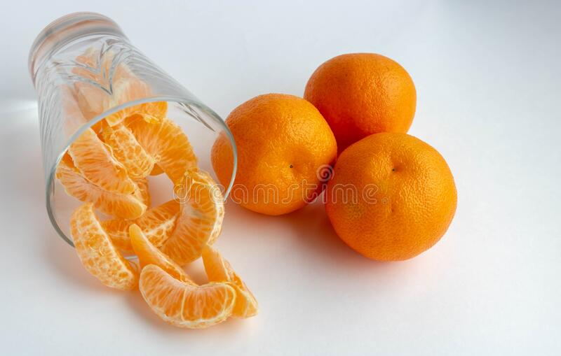 Citrus juice in a clear glass on a light white background. Mandarin, orange close-up. Fruits. Fruits with a high content of. Vitamin C.food royalty free stock images