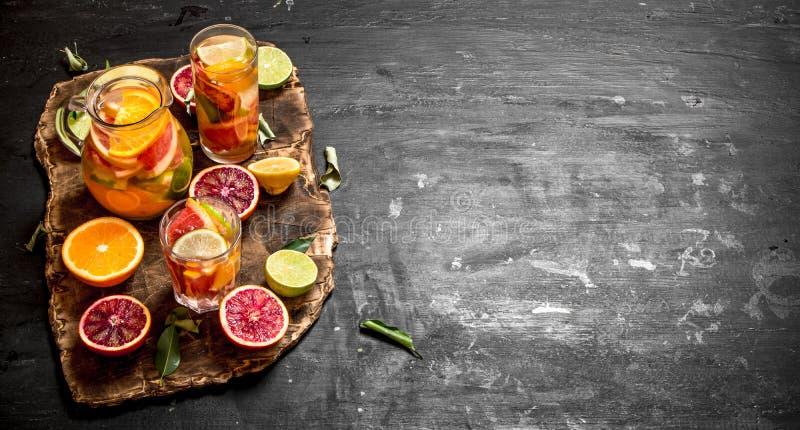 citrus klar text för bakgrund Ny citrus fruktsaft med skivor av limefrukter, apelsiner, grapefrukter och citroner arkivbilder