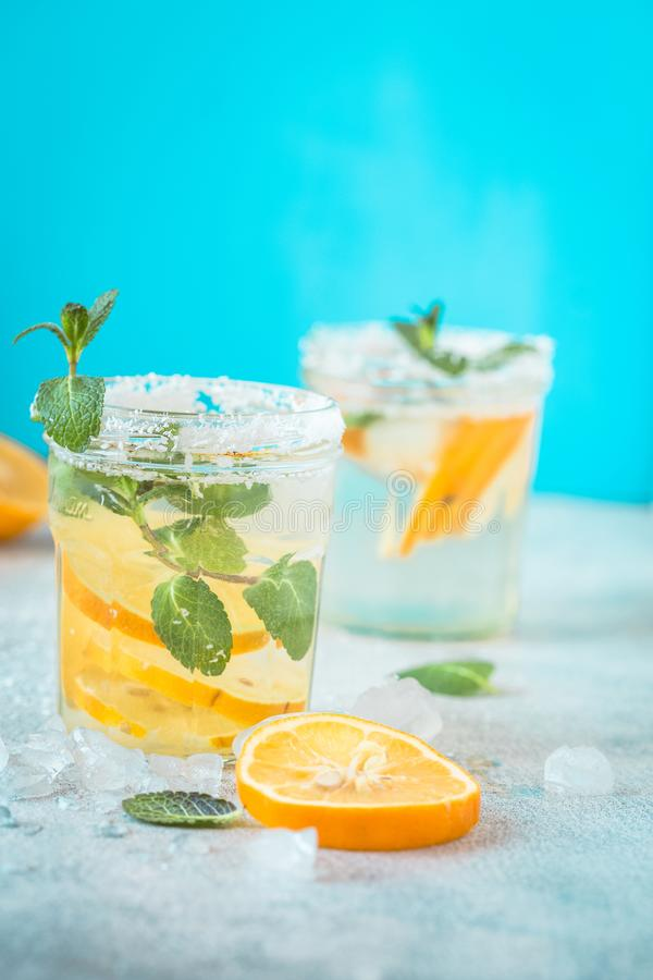 Free Citrus Lemonade Water With Lemon Sliced Healthy And Detox Water Drink In Summer On Wooden Table With Blue Lighten Background Royalty Free Stock Photos - 115032118