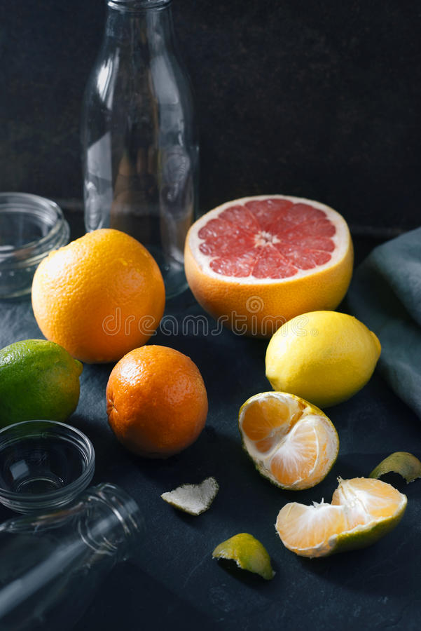 Citrus mix with empty glass bottle on the dark stone background stock image