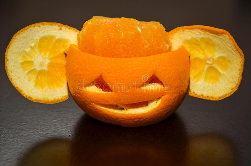 Citrus orange fruit carved as a pumpkin face royalty free