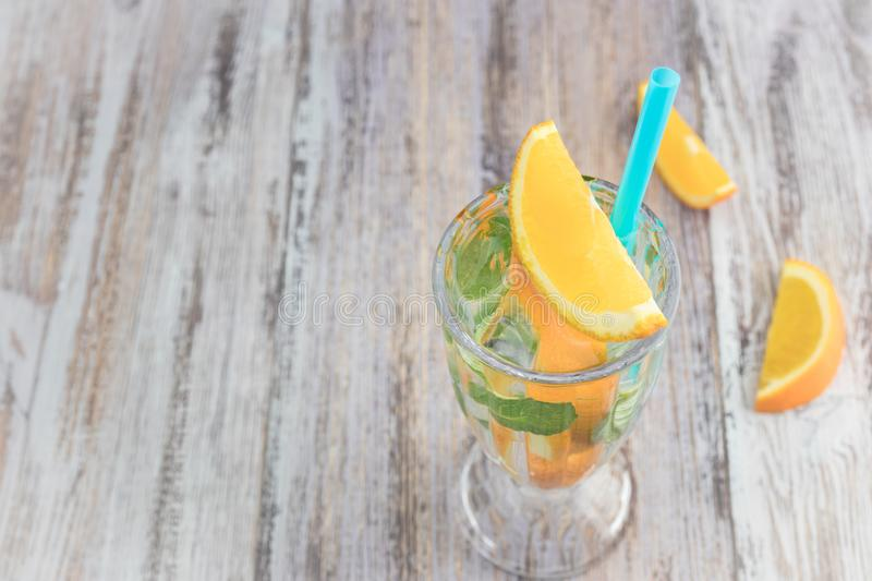 Citrus refreshing drink in a glass goblet on a wooden table. summer refreshing cocktail. Healthy food, drinks. orange and mint ice stock images