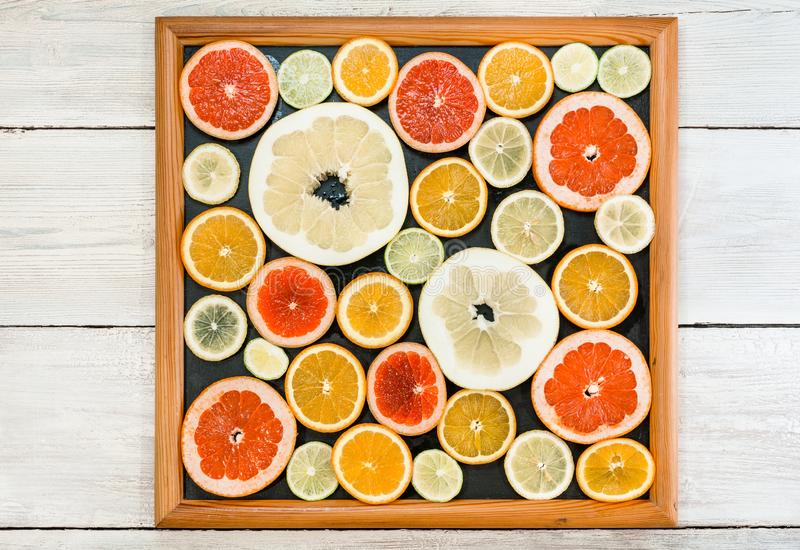 Citrus slices in picture frame. Fresh citrus fruits in different colours and sizes, cut into slices and laid out in a royalty free stock photo