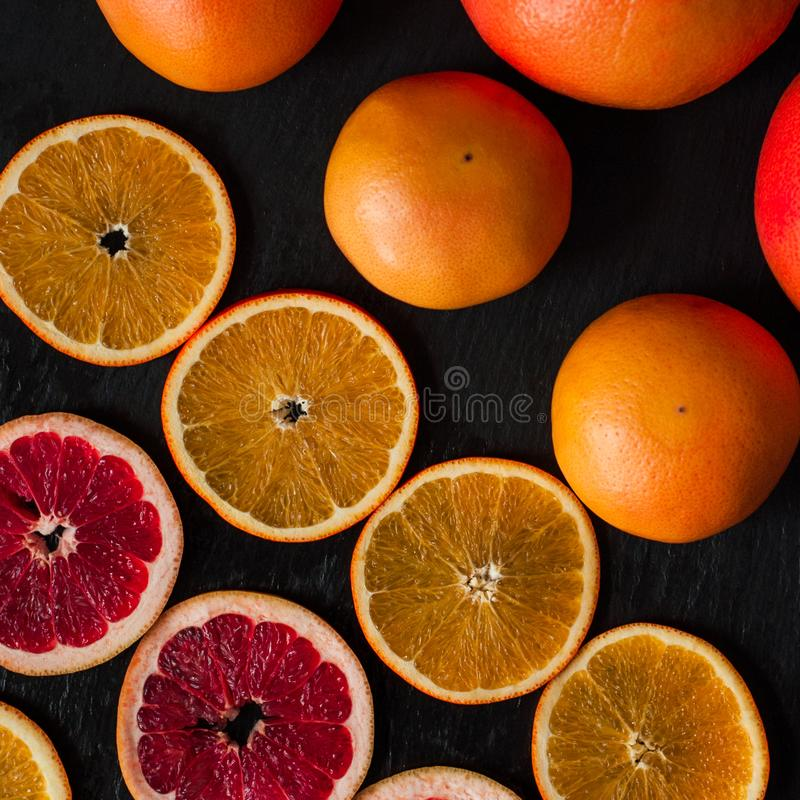 Citrus flatlay on dark rustic background. Sliced and whole oranges and grapefruits. stock photography