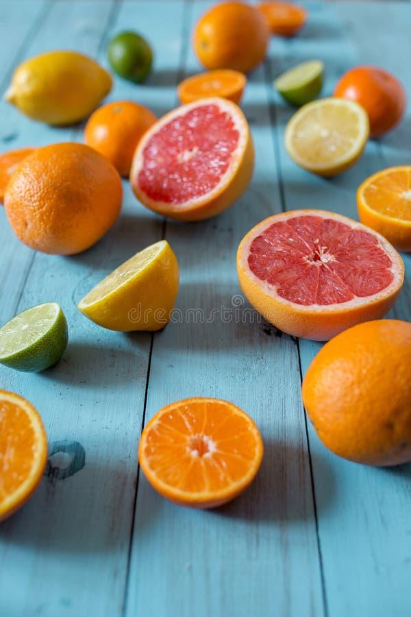 Citrusfrukter helt och skivat på blå träbakgrund Selektivt fokusera royaltyfri foto