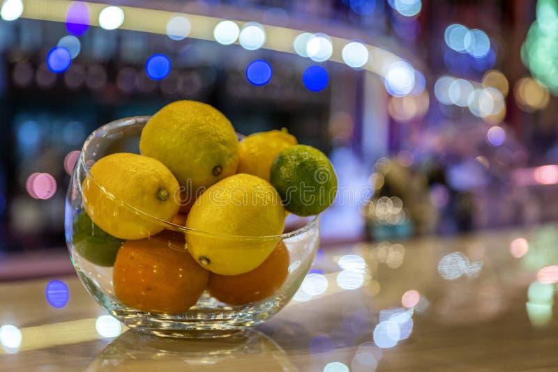 Citrusfrukter i en vas på en tabell i en restaurang Härlig mångfärgad festlig bokeh på bakgrund fotografering för bildbyråer
