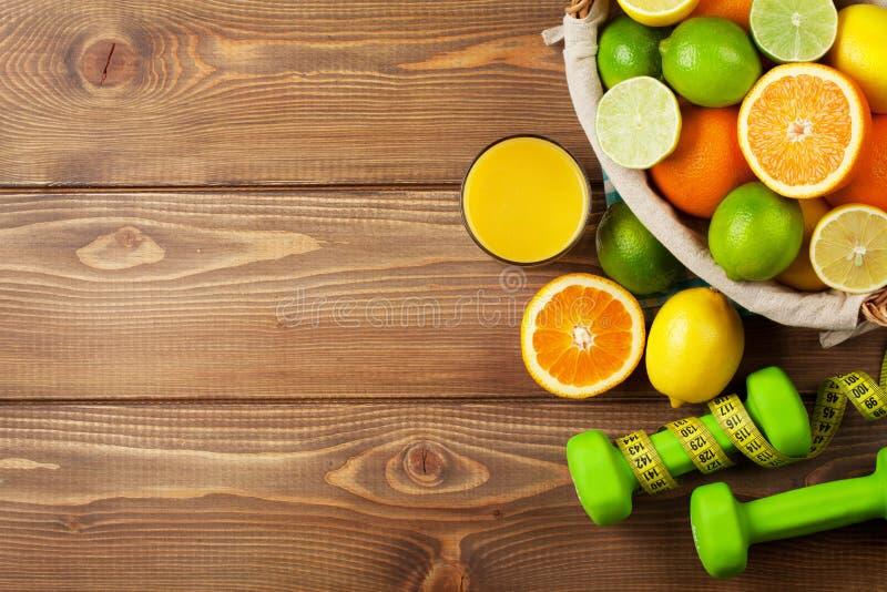 Citrusfrukter i korg och dumbells Apelsiner, limefrukter och citroner fotografering för bildbyråer