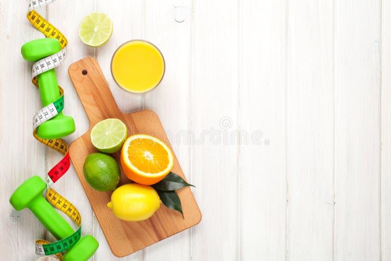 Citrusfrukter, måttband och dumbells royaltyfri foto
