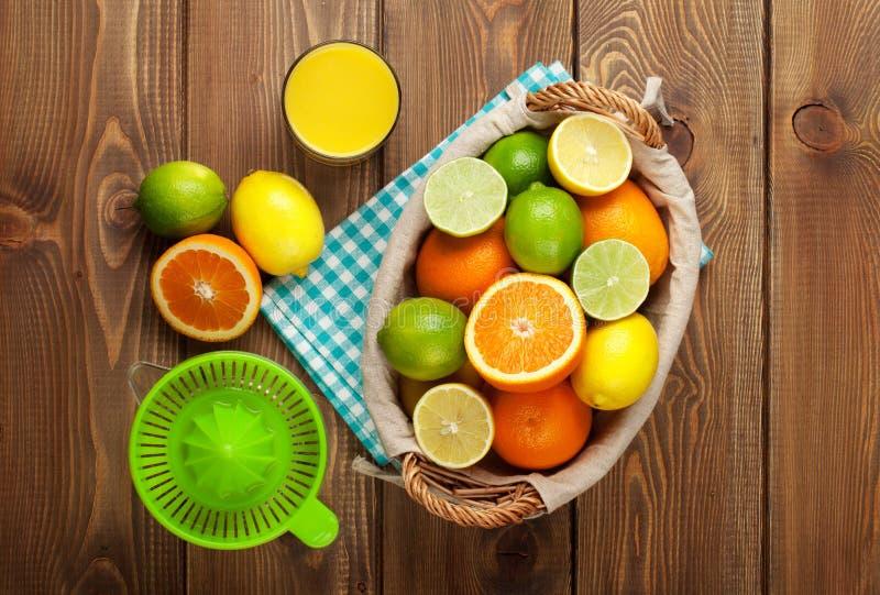 Citrusfrukter och exponeringsglas av fruktsaft Apelsiner, limefrukter och citroner royaltyfri fotografi