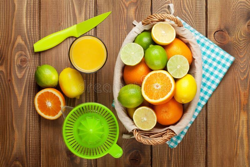 Citrusfrukter och exponeringsglas av fruktsaft Apelsiner, limefrukter och citroner royaltyfri foto