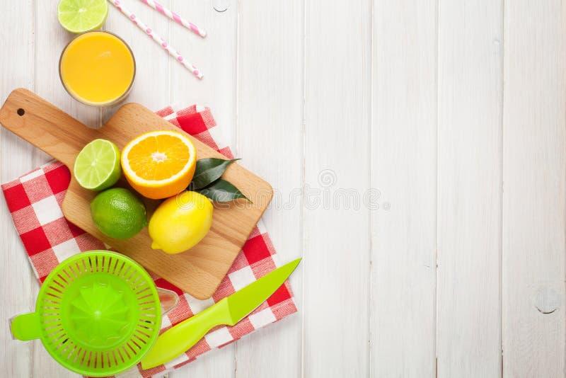 Citrusfrukter och exponeringsglas av fruktsaft Apelsiner, limefrukter och citroner arkivbild