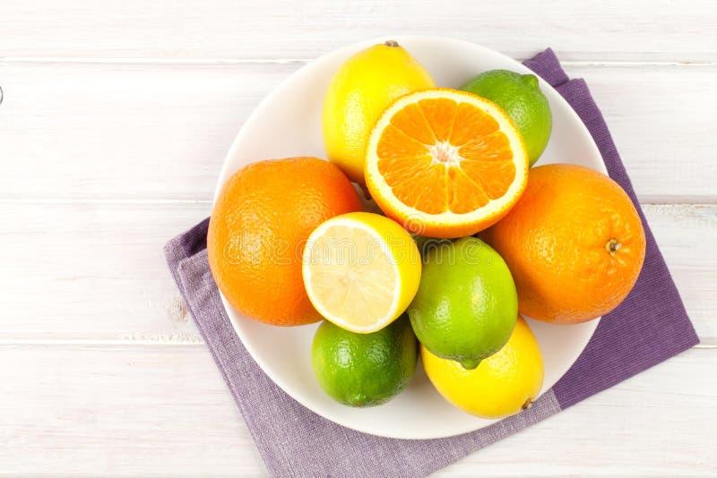 Citrusfrukter på plattan Apelsiner, limefrukter och citroner royaltyfria foton