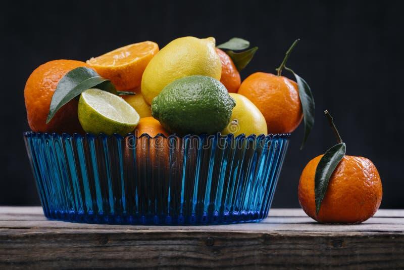 Citrusvrucht in blauwe glaskom stock afbeeldingen