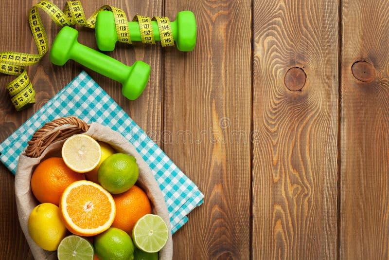 Citrusvruchten in mand en dumbells Sinaasappelen, kalk en citroenen stock afbeeldingen