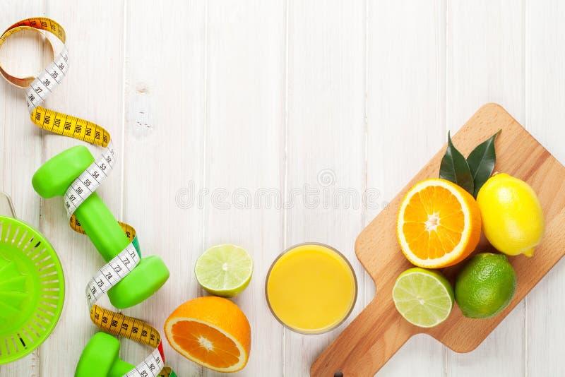 Citrusvruchten, meetlint en dumbells stock afbeelding