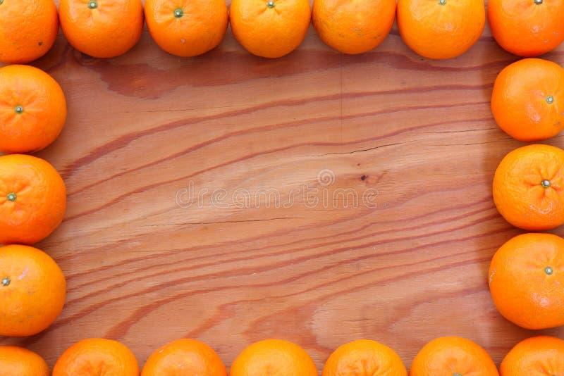 Citrusvruchten tankan vierkant kader tegen houten achtergrond stock fotografie
