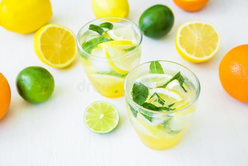 Citrusvruchtenlimonade met kalk, munt en citroenen in glazen op witte lijst royalty-vrije stock afbeeldingen