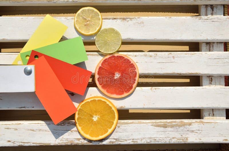 Citrusvruchtenplakken op houten oppervlakte met document kleurenkaart royalty-vrije stock afbeelding