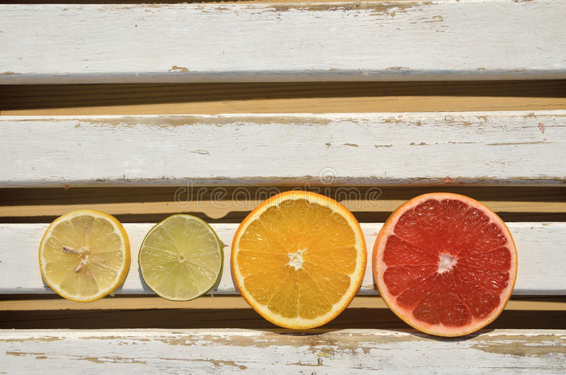 Citrusvruchtenplakken op witte houten oppervlakte stock afbeeldingen