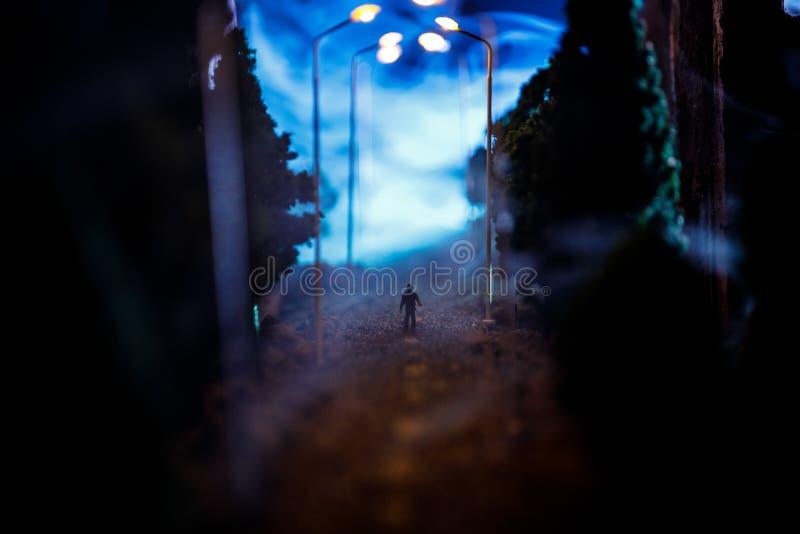 Città alla notte in nebbia densa Smog spesso su una via scura Siluette dell'uomo sulla strada Decorazione della Tabella Fuoco sel fotografia stock