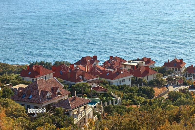 Città del cottage sul pendio di collina nei precedenti del mare immagini stock