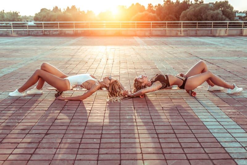 Città dell'estate di due la bella amiche delle ragazze, prende il sole bordi del pattino di longboard delle mattonelle del fondo  fotografie stock