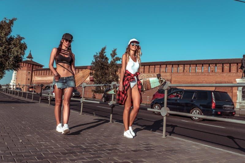 Città dell'estate di due la bella amiche delle ragazze, va vicino alla strada, le automobili del fondo, bordi del pattino di long fotografie stock