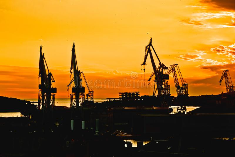 Città della vista della siluetta di tramonto delle gru del cantiere navale di Pola fotografia stock