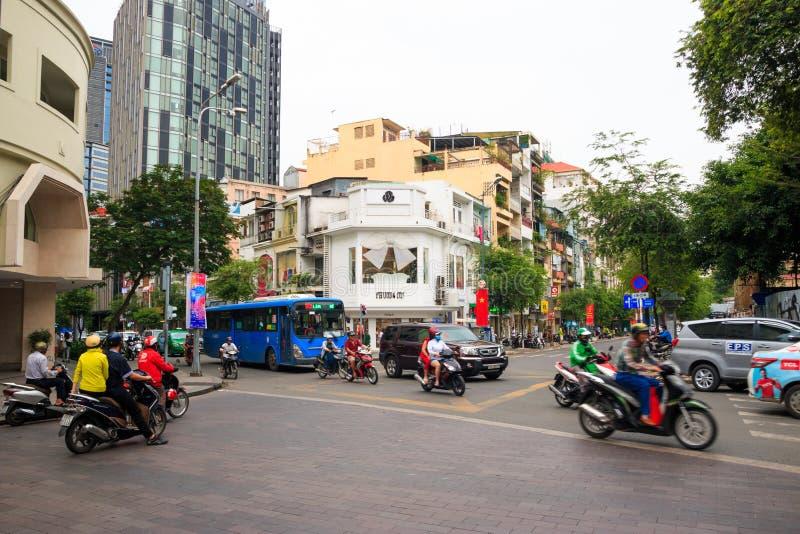 Città di Ho Chi Minh, Vietnam - dicembre 2018: negozio bianco con il grande arco sulla strada trasversale con traffico, le motoci immagine stock libera da diritti
