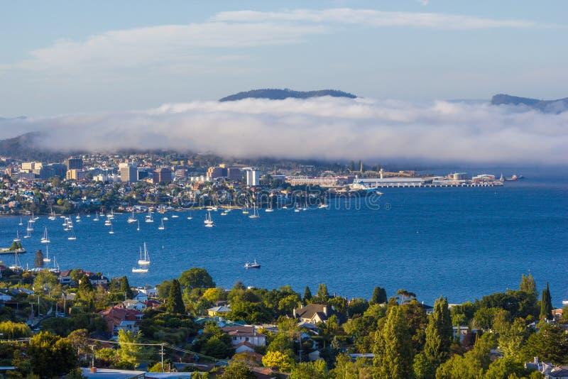 Città di Hobart e fiume derwent osservati da sobborgo della baia sabbiosa con la foschia del mare che si rivolta riva orientale fotografie stock