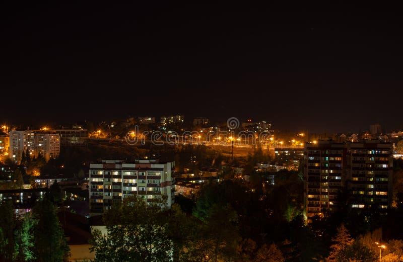 Città di notte con le luci, i grattacieli illuminati e gli alberi immagini stock