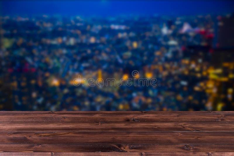 Città di notte della sfuocatura con la tavola di legno f immagini stock