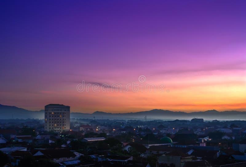 Città di Purwokerto ad alba Siluetta dell'uomo Cowering di affari immagine stock