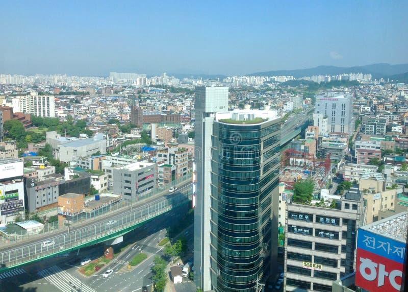 Città di Suwon un bello giorno del cielo blu che guarda giù alle costruzioni, al traffico ed alle zone residenziali immagini stock