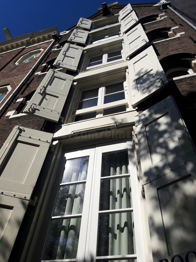 Città storica con gli otturatori di legno della finestra aperti Otturatori sulle finestre di una città europea, Amsterdam fotografia stock