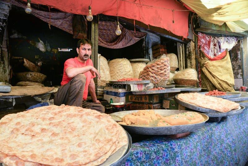 CITTÀ VECCHIA, SRINAGAR, INDIA MAGGIO 2017: Commerciante nella stalla dell'alimento nel mercato di Srinagar immagine stock libera da diritti