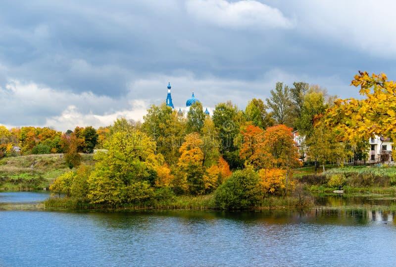 Cittadina con una chiesa sulla riva del lago di caduta immagini stock libere da diritti