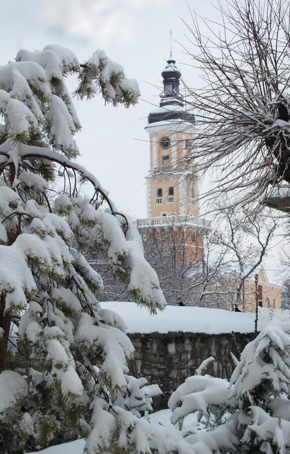 City bell tower, snowy fir trees, winter, tracks in the snow. Church in the snow, religion, christmas, big snowy trees, winter morning, snowy royalty free stock photos