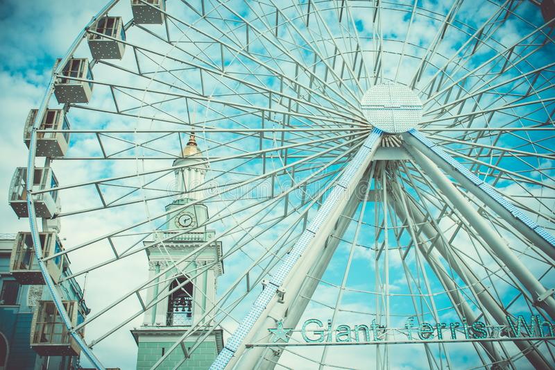 City ​​turquoise ferris wheel on the background of the church royalty free stock photography