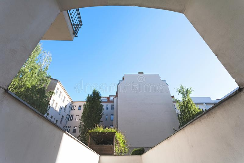 City apartment building yard, on a clear, blue sunny day, perspective from a garage driveway. A city apartment building yard, on a clear, blue sunny day stock image