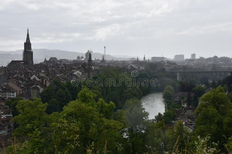 The city of Bern and the river Aare in rain. View of the city of Bern and the river Aare on a rainy day with Berner Münster in reconstruction stock photography
