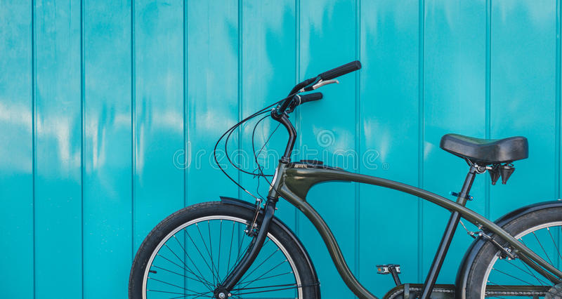 City Bicycle Parked Near Blue Wall, Daily Lifestyle Urban Concept. Green urban bike cruiser parked near blue wall stock photo