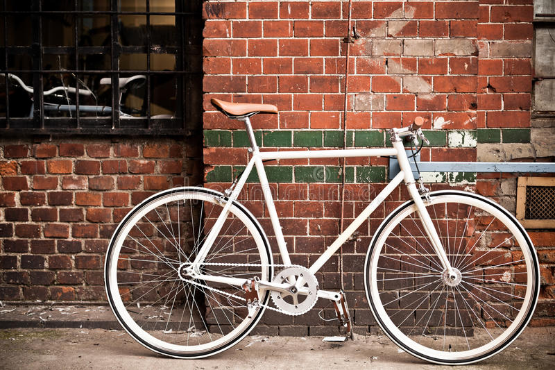City bicycle on red wall, vintage. City bicycle fixed gear and red brick wall stock photography