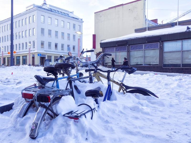 City bikes covered on snow in a street royalty free stock photo