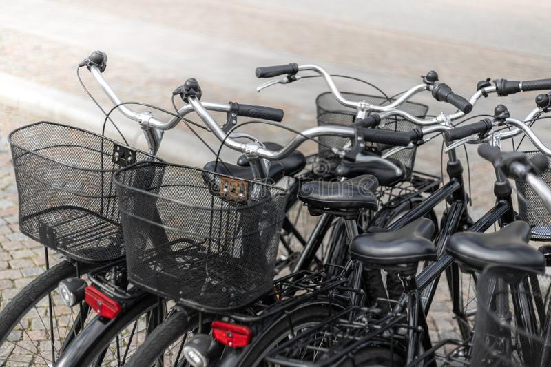 City Bikes Parked on Paved Road. City bikes with baskets parked on paved road royalty free stock photography